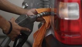 Um frentista enche o tanque de um carro na praia do Leme, no Rio de Janeiro. O Índice Nacional de Preços ao Consumidor Amplo-15 (IPCA-15), prévia da inflação oficial do país, surpreendeu ao acelerar a alta mensal a 0,75 por cento em dezembro, fechando o ano em 5,85 por cento e levantando a possibilidade de que o IPCA pode não encerrar 2013 abaixo do que foi visto no ano passado. 30/03/2011 REUTERS/Ricardo Moraes
