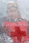 Президент России Владимир Путин виден сквозь покрытое снегом стекло кабины подъёмника в горах у черноморского курорта Сочи 20 февраля 2007 года. Игры в Сочи - знак похолодания инвестклимата России ниже нуля, считает колумнист Reuters Breakingviews Пьер Бриансон. REUTERS/Artyom Korotayev