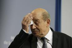 France's Defence Minister Jean-Yves Le Drian wipes his face as he attends a news conference in Paris October 3, 2013. REUTERS/Gonzalo Fuentes