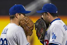 Los Angeles Dodgers starting pitcher Ted Lilly and first baseman Adrian Gonzalez (R) use their gloves to hide their conversation on the mound during the second inning of their MLB National League game against the New York Mets at CitiField in New York April 24, 2013. REUTERS/Ray Stubblebine
