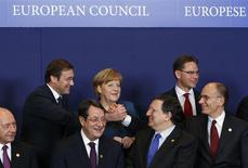 (L-R) Romania's President Traian Basescu, Portugal's Prime Minister Pedro Passos Coelho, Cyprus' President Nicos Anastasiades, Germany's Chancellor Angela Merkel, European Commission President Jose Manuel Barroso, Finland's Prime Minister Jyrki Katainen and Italy's Prime Minister Enrico Letta take part in a family photo session during a European Union leaders summit at the EU council headquarters in Brussels December 19, 2013. REUTERS/Yves Herman