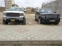 A 2013 Ford F-150 special edition truck (R) and a GMC truck are seen outside an auto dealership in Aras free zone in northwest Iran in this handout photo made available to Reuters in December 2013. REUTERS/Sajad Roshandel/Handout