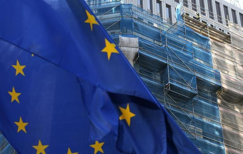 A European Union flag flutters as a construction worker is seen on a building under renovation in Brussels December 9, 2013 file photo. REUTERS/Francois Lenoir
