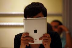 A man looks at his iPad while sitting in a cafe in central Beijing June 6, 2012. REUTERS/David Gray