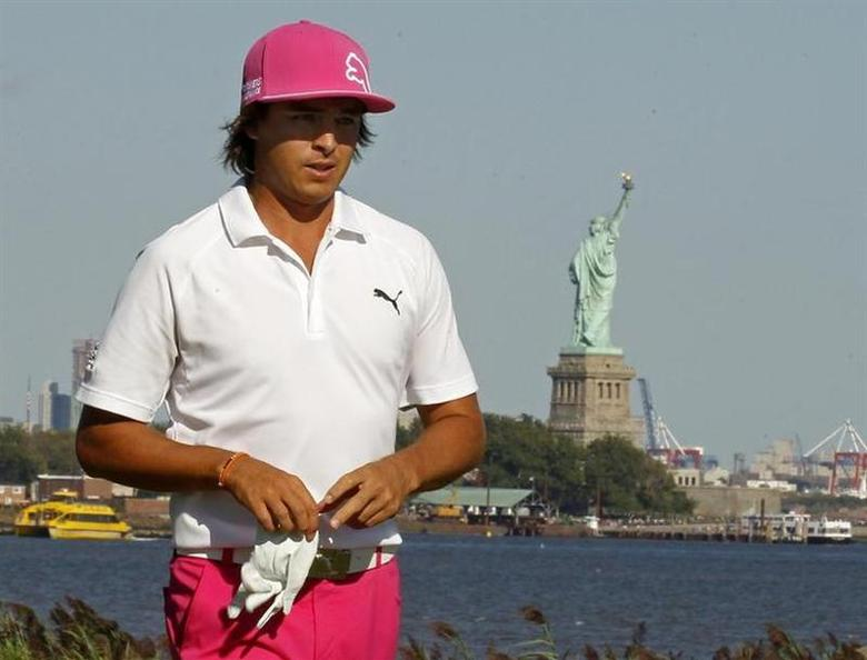 Rickie Fowler of the U.S. walks off the 14th green during the third round of the Barclays PGA golf tournament in Jersey City, New Jersey August 24, 2013. The Statue of Liberty is pictured in the background. REUTERS/Adam Hunger