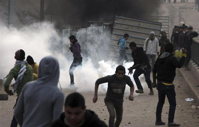 Supporters of the Muslim Brotherhood and ousted Egyptian President Mohamed Mursi flee after riot police fired tear gas during clashes in Cairo December 20, 2013. REUTERS/Stringer