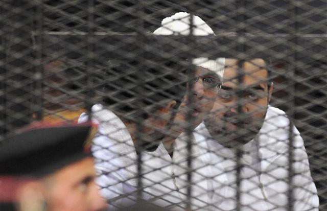 Political activists Ahmed Maher, Ahmed Douma (L) and Mohamed Adel (R) of the 6 April movement look on from behind bars in Abdeen court in Cairo, December 22, 2013. REUTERS/Stringer
