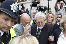 Entertainer Rolf Harris is surrounded by members of the media as he leaves Westminster Magistrates Court, in central London September 23, 2013. REUTERS/Neil Hall
