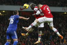 Arsenal's Bacary Sagna (C) and Thomas Vermaelen (R) jump to head the ball as Chelsea's John Terry looks on during their English Premier League soccer match at The Emirates in London December 23, 2013. REUTERS/Andrew Winning