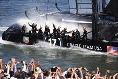 Members of Oracle Team USA wave to spectators after winning Race 16 of the 34th America's Cup yacht sailing race against Emirates Team New Zealand in San Francisco, California September 23, 2013. REUTERS/Stephen Lam