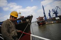 A labourer walks near a ship which is under construction at the Hudong-Zhonghua Shipbuilding company's shipyard in Shanghai October 14, 2013. REUTERS/Carlos Barria