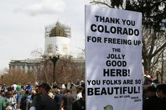 A man holds a sign referring to Colorado legalizing marijuana with the state capitol dome in the background at the 4/20 marijuana holiday in Civic Center Park in downtown Denver April 20, 2013. REUTERS/Rick Wilking