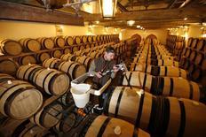 Los problemas económicos en Francia, el mercado de origen del champagne, le restaron efervescencia a las ventas globales de la prestigiosa bebida por segundo año consecutivo en el 2013 y el dinamismo de las exportaciones a nuevos mercados no logró contrarrestar el descenso. En la foto de archivo, un trabajador llena un barril de champagne en la viña Billecart-Salmon en Mareuil-sur-Ay. Oct 7, 2013. REUTERS/Benoit Tessier
