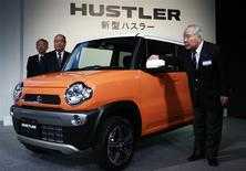 "Suzuki Motor Corp Chairman and Chief Executive Officer Osamu Suzuki (R), Executive Vice President Minoru Tamura (C), and Executive Vice President Osamu Honda pose next to the new boxy minicar ""Hustler"" during its unveiling event in Tokyo December 24, 2013. REUTERS/Yuya Shino"