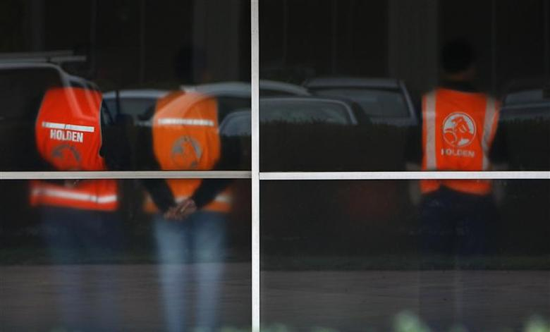 Workers wearing safety vests are seen through frosted windows at the General Motors Holden offices in Melbourne in this June 2, 2009 file photo. REUTERS/Mick Tsikas