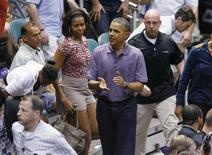 President Barack Obama claps after he and the First Family watched the Diamond Head basketball game between Oregon State Beavers and Akron Zips during their Christmas vacation in Honolulu, Hawaii, December 22, 2013. REUTERS/Hugh Gentry
