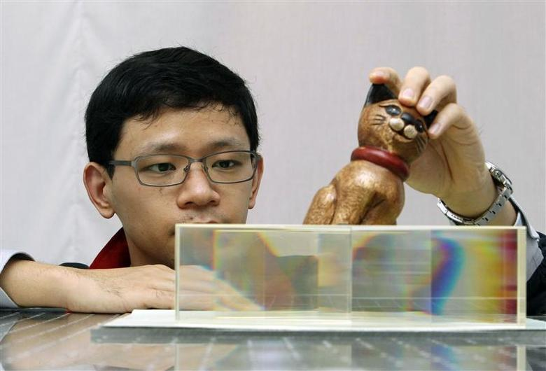 Nanyang Technological University (NTU) School of Physical and Mathematical Science researcher Zhang Baile shows how light passes through a set of carefully angled glass blocks to render an object invisible as he talks to the media about his research at NTU in Singapore November 7, 2013. REUTERS/Edgar Su