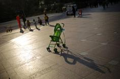 A baby stroller is seen as mothers play with their children at a public area in downtown Shanghai November 19, 2013. REUTERS/Carlos Barria