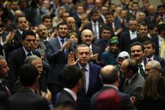 Премьер-министр Турции Тайип Эрдоган приветствует однопартийцев на встрече в штаб-квартире правящей партии AK Party в Анкаре 25 декабря 2013 года. Премьер-министр Турции Тайип Эрдоган в среду реформировал кабинет, после того как три министра ушли в отставку из-за коррупционного скандала, который стал беспрецедентной угрозой его 11-летнему правлению. REUTERS/Umit Bektas