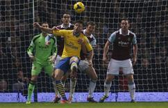 Arsenal's Olivier Giroud (C) challenges West Ham United's Joey O'Brien (2nd L) and West Ham United's George McCartney (2nd R) during their English Premier League soccer match at Upton Park in London December 26, 2013. REUTERS/Suzanne Plunkett