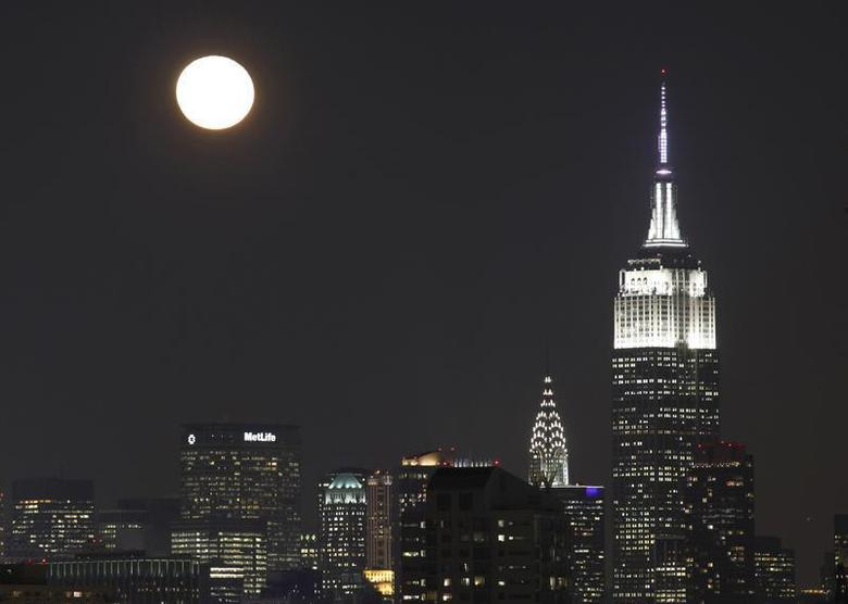 The moon rises behind the skyline of New York and the Empire State Building (R), as seen from Jersey City, New Jersey, December 18, 2013. REUTERS/Gary Hershorn