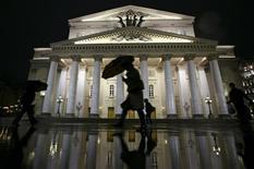 Человек идет мимо Большого театра дождливым московским вечером 12 октября 2011 года. Погода и температура воздуха в Москве на выходных останется такой же, как и в течение рабочей недели, прогнозируют синоптики. REUTERS/Anton Golubev