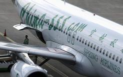 Funcionário da Spring Airlines próximo de uma aeronave Airbus A320 no aeroporto de Hongqiao, em Xangai. A aérea chinesa de baixo custo Spring Airlines recebeu aprovação para uma joint venture japonesa que deve começar a voar em maio. 06/07/2012 REUTERS/Aly Song