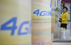 Consumidor observa anúncios sobre 4G em pilares dentro de um shopping em Taiyuan, na província de Shanxi. O investimento na rede de telefonia móvel 4G da China pode chegar a 100 bilhões de iuanes (16,5 bilhões de dólares) no ano que vem, com o número de usuários alcançando 30 milhões em mais de 300 cidades, relatou a agência de notícias oficial Xinhua, atribuindo a fala ao ministro da Indústria e Tecnologia da Informação nesta sexta-feira. 05/12/2013 REUTERS/Jon Woo