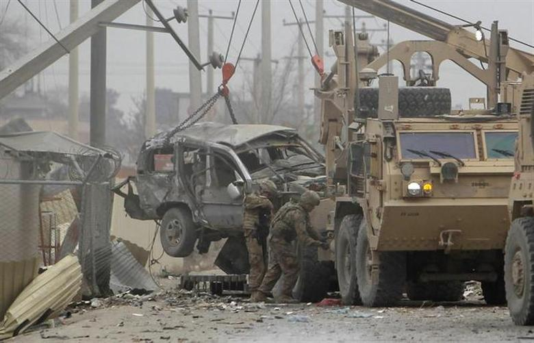 U.S. trucks lift up an armoured vehicle hit by a bomb attack in Kabul December 27, 2013. REUTERS/Omar Sobhani