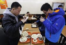 Diners take pictures of steamed buns which Chinese President Xi Jinping ate on Saturday, at the Qing-Feng steamed buns restaurant in Beijing, December 29, 2013. REUTERS/Kim Kyung-Hoon