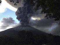 The Chaparrastique volcano, behind electricity cables, spews ash at the municipality of San Miguel December 29, 2013. REUTERS/Stringer