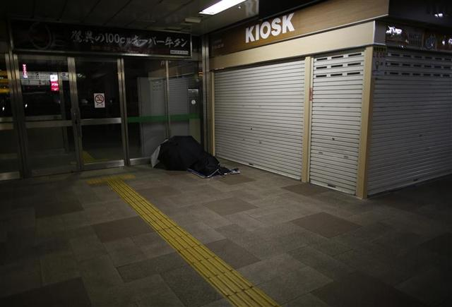 A homeless man rests on the ground at a concourse of Sendai Station in Sendai, northern Japan December 17, 2013. REUTERS/Issei Kato