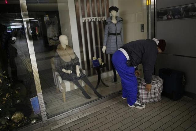 Shizuya Nishiyama, a 57-year-old homeless man from Hokkaido, clears his belongings away in front of a clothes shop at Sendai Station in Sendai, northern Japan December 18, 2013. REUTERS/Issei Kato
