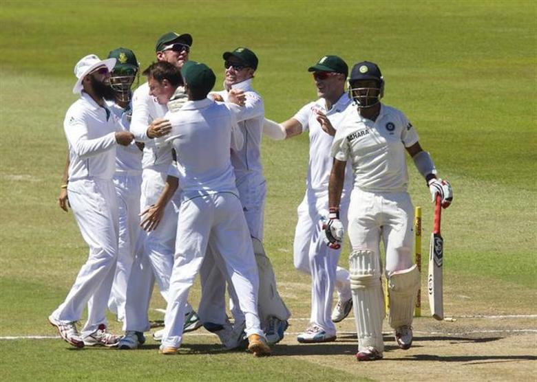 South Africa's players celebrate the wicket of India's Cheteshwar Pujara (R) during the fifth day of the second test cricket match in Durban, December 30, 2013. REUTERS/Rogan Ward