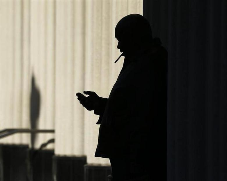 A man sends text messages on his mobile phone as he smokes a cigarette outside the court building in San Diego, California December 9, 2013. REUTERS/Mike Blake