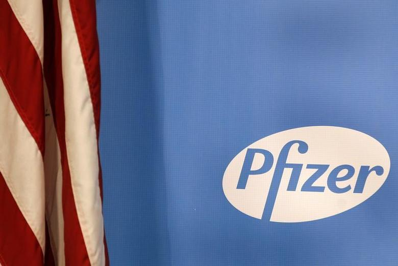 The Pfizer logo is seen next to a U.S. flag in a conference room at their world headquarters in New York November 5, 2013. REUTERS/Adam Hunger