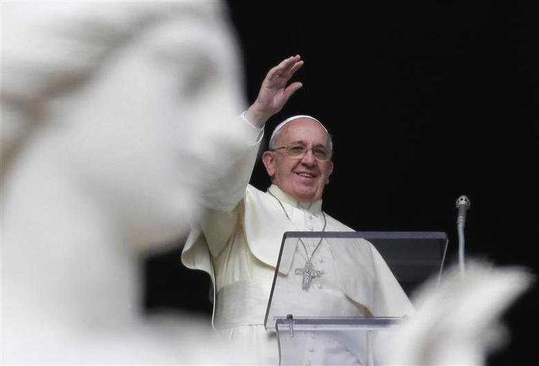 Pope Francis waves as he leads the Angelus prayer from the window of the Apostolic palace in Saint Peter's Square at the Vatican December 29, 2013. REUTERS/Max Rossi