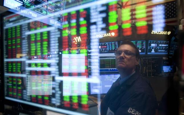 A trader is reflected in a screen as he works on the floor of the New York Stock exchange in New York, December 27, 2013. REUTERS/Carlo Allegri