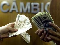 Consumidores trocam real por dólar em casa de câmbio no Rio de Janeiro, em agosto de 2003. 04/08/2003 REUTERS/Bruno Domingos