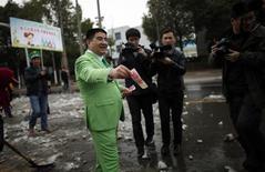 El multimillonario chino Chen Guangbiao entrega dinero a los barrenderos durante un evento organizado por él donde criticó a las compañías que afirma están contaminando el medioambiente. 21 de febrero, 2013. El excéntrico magnate chino del reciclaje dijo que se preparaba para comenzar negociaciones para comprar al diario estadounidense New York Times Co. Guangbiao, un conocido filántropo, es como una celebridad en China. REUTERS/Carlos Barria (CHINA - MEDIOAMBIENTE NEGOCIOS SOCIEDAD)