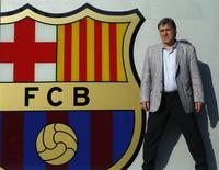 """Argentine soccer coach Gerardo """"Tata"""" Martino poses next to Barcelona's logo in front of their offices in Barcelona July 25, 2013. REUTERS/Albert Gea"""
