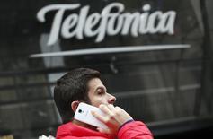 """Homem conversa em celular enquanto passa pela principal loja do grupo espanhol de telecomunicações Telefónica, no centro de Madri, 8 de novembro de 2013. A Telefónica está trabalhando em uma oferta conjunta para assumir a TIM Participações e quebrar a unidade wireless local da Telecom Itália, também conhecida como TIM Brasil, disse um jornal italiano nesta sexta-feira citando """"fontes confiáveis"""". 08/11/2013 REUTERS/Sergio Perez"""