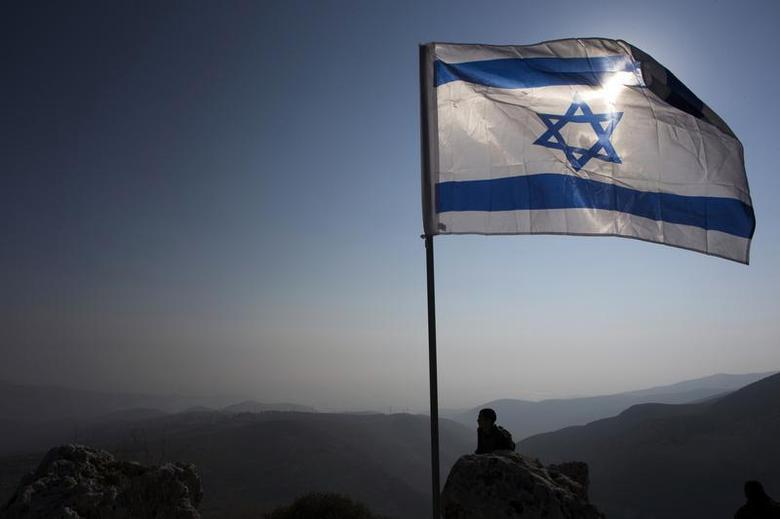An Israeli soldier stands guard under an Israeli national flag during a tour made by Israeli parliament members in the Jordan Valley near the Jewish settlement of Maale Efrayim January 2, 2014. REUTERS/Ronen Zvulun