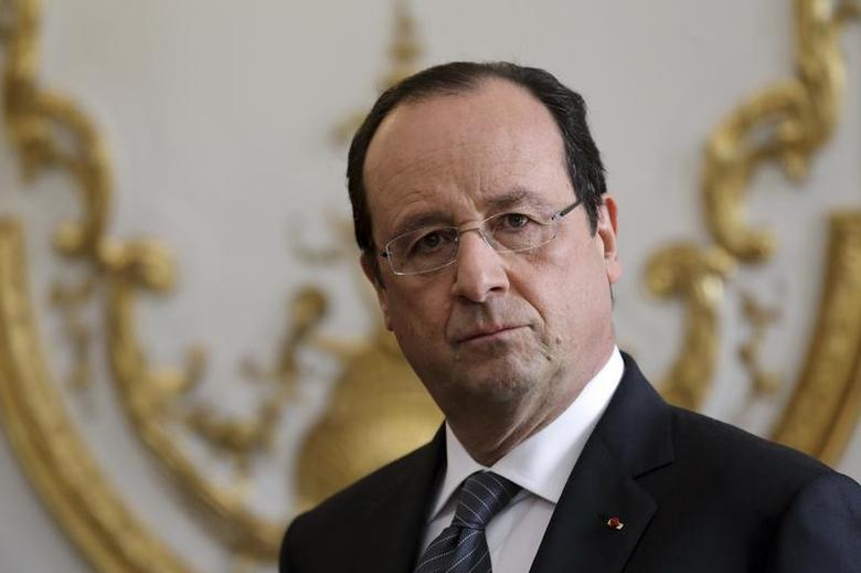 French President Francois Hollande listens to the speech of French Prime Minister during a new year ceremony with members of the government at the Elysee Palace in Paris, January 3, 2014. REUTERS/Philippe Wojazer
