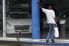 A man looks at the price of Peugeot cars in Havana January 3, 2014. REUTERS/Enrique de la Osa