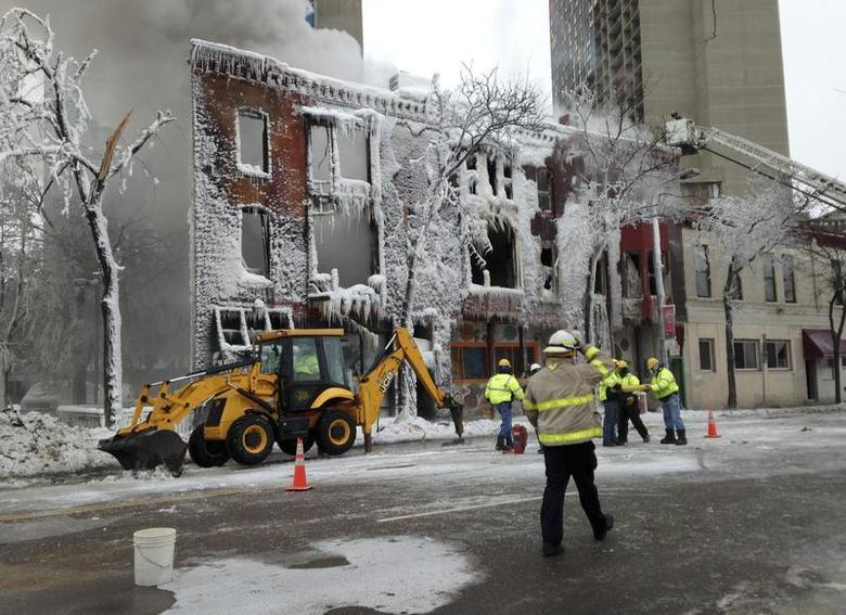 Emergency workers stand outside an apartment building which was destroyed by an explosion and a fire in Minneapolis January 1, 2014. REUTERS/David Bailey
