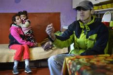 Jozef Bartos (R), a 20-year-old Roma, is pictured with his wife and child in their shack that has no running water or sewerage in Cierny Balog December 11, 2013. REUTERS/Radovan Stoklasa