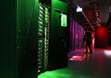 """Membro da imprensa filma a sala que tem o IBM Blue Gene Q Supercomputer no dia do lançamento do HBP na EPFL em Ecublens. Os gastos com Tecnologia da Informação (TI) em todo o mundo deverão crescer 3,1 por cento este ano, a 3,8 trilhão de dólares, depois de um 2013 estável, e serão impulsionados por empresas que começam a aproveitar a """"big data"""" de smartphones e outros dispositivos, disseram analistas da Gartner nesta segunda-feira. 07/10/2013 REUTERS/Denis Balibouse"""