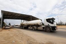 Un camión saliendo de la refinería de petróleos y terminal porturario de Zawiya, Libia, dic 18 2013. La producción de petróleo de la OPEP cayó en diciembre a su menor nivel desde mayo del 2011 debido a las huelgas y protestas en Libia, al estancamiento en las exportaciones de Irak y por una mayor reducción de la oferta de Arabia Saudita, mostró el lunes un sondeo de Reuters. REUTERS/Ismail Zitouny