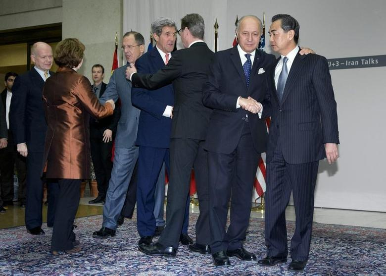 (L-R) British Foreign Secretary William Hague, EU foreign policy chief Catherine Ashton, Russia's Foreign Minister Sergei Lavrov, U.S. Secretary of State John Kerry, Germany's Foreign Minister Guido Westerwelle, French Foreign Minister Laurent Fabius and Chinese Foreign Minister Wang Yi shake hands after Ashton read a statement to the media at the United Nations Palais in Geneva November 24, 2013. REUTERS/Carolyn Kaster/Pool